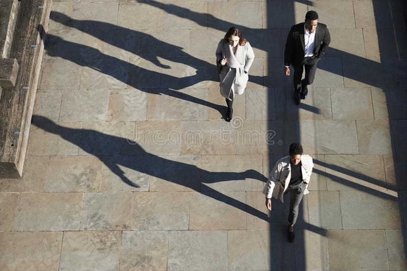 Aerial view of three city workers walking on a sunny urban street, horizontal royalty free stock photos