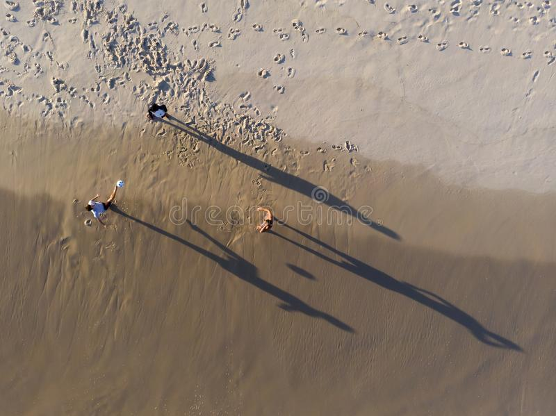 Aerial view of three men playing Altinha, a common beach sport in Rio, in Barra da Tijuca beach during late afternoon. royalty free stock photography