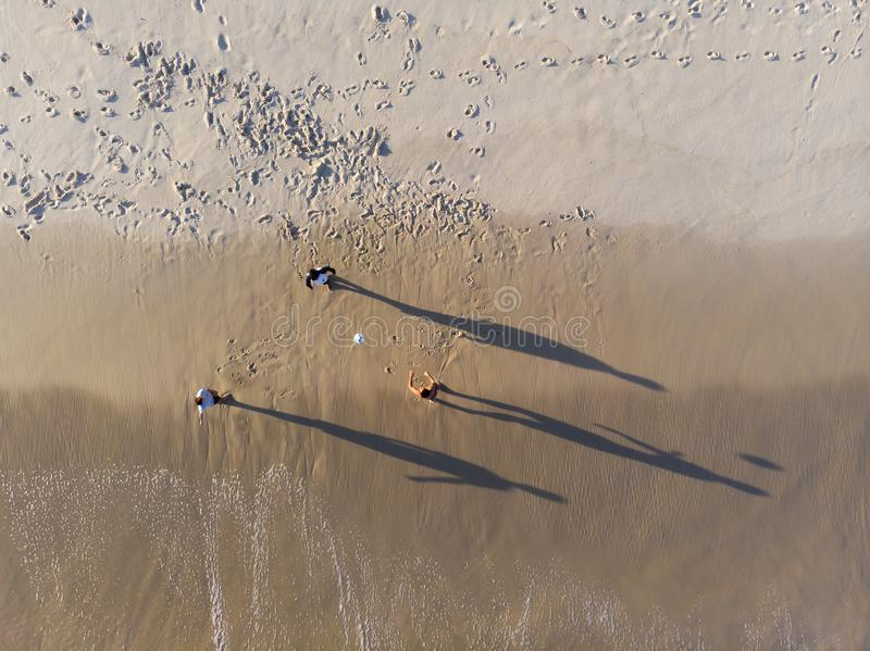 Aerial view of three men playing Altinha, a common beach sport in Rio, in Barra da Tijuca beach during late afternoon. stock photography