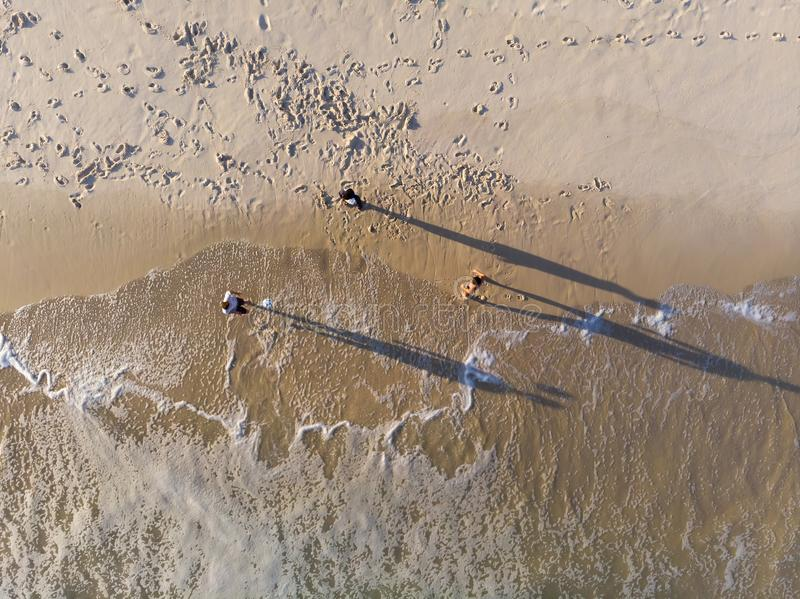 Aerial view of three men playing Altinha, a common beach sport in Rio, while wave crashes in Barra da Tijuca beach during late aft royalty free stock photos