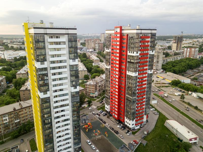 Aerial view of three tall skyscrapers of red, green and yellow colors. Aerial view of landscape with two tall skyscrapers of red and yellow colors among small stock images