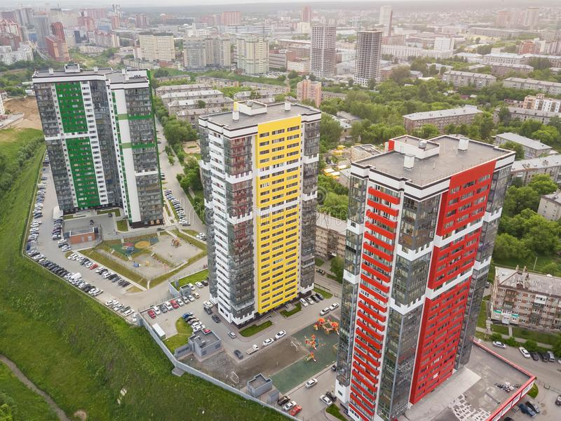Aerial view of three tall skyscrapers of red, green and yellow colors. Among small buildings with parking for cars and a children`s playground in the yard with royalty free stock photography