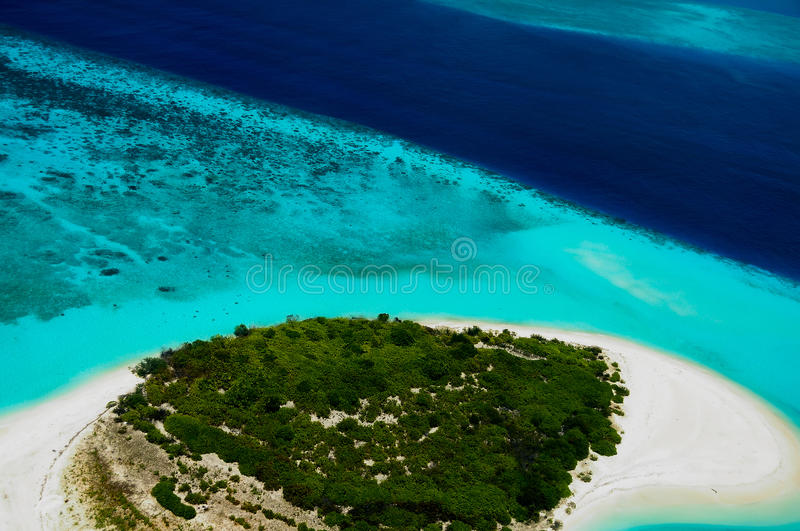 Aerial view to desert Maldivian islland. Aerial view to green desert Maldivian islland surrounded by blue ocean water royalty free stock photo