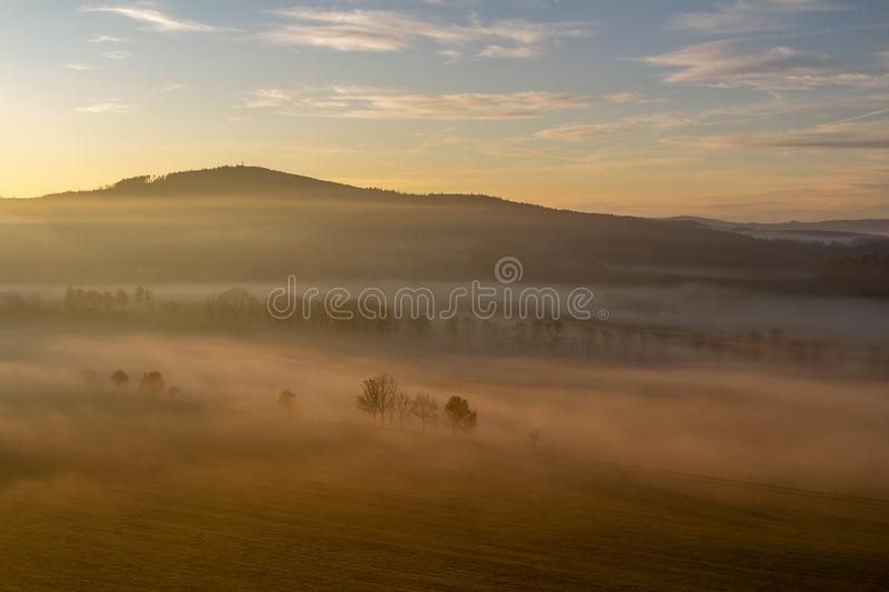 Aerial view to trees silhouette in misty orange fog at sunrise, Czech landscape.  stock images