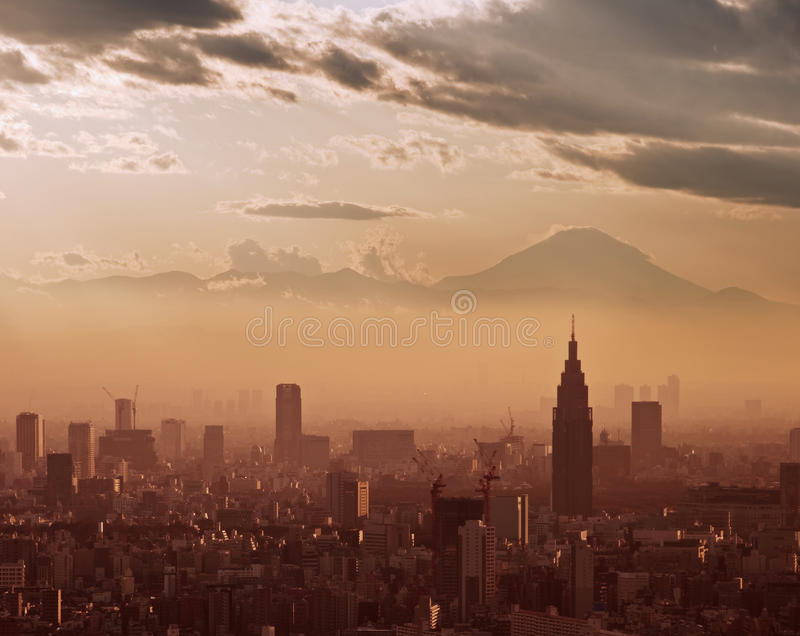 Aerial view of Tokyo at sunset, with the silhouette of Mount Fuji. In the background royalty free stock photography