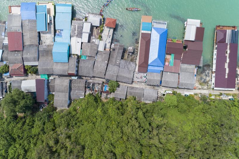 Aerial view top view of the fisherman village with fishing boats and house's roof at the pier in koh rat suratthani Thailand.  royalty free stock image
