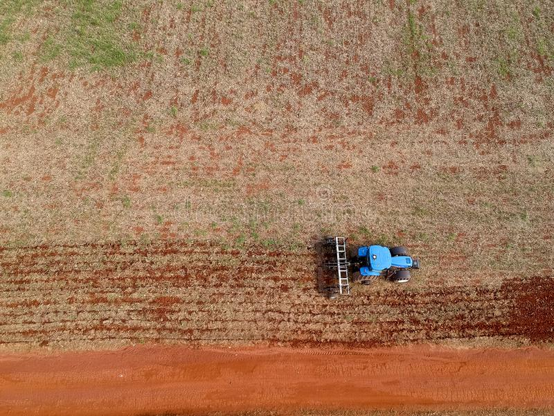 Aerial view of a tractor harrowing the soil to plant soybeans stock image