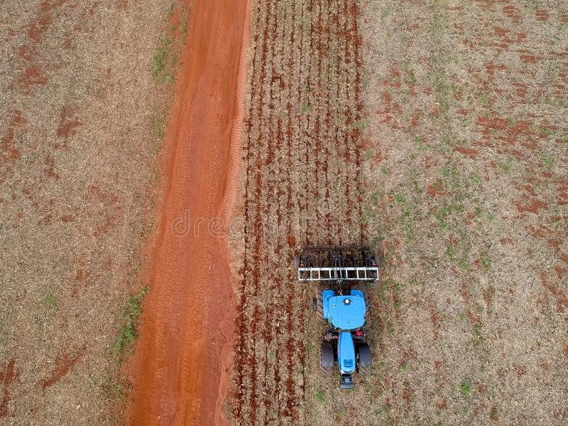 Aerial view of a tractor harrowing the soil to plant soybeans royalty free stock image
