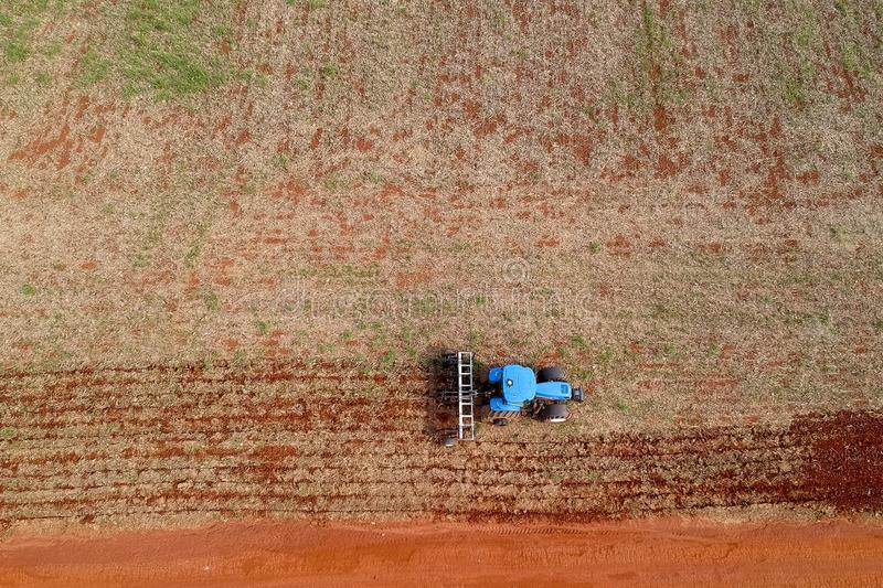 Aerial view of a tractor harrowing the soil to plant soybeans stock photography