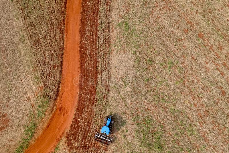 Aerial view of a tractor harrowing the soil to plant soybeans stock photo