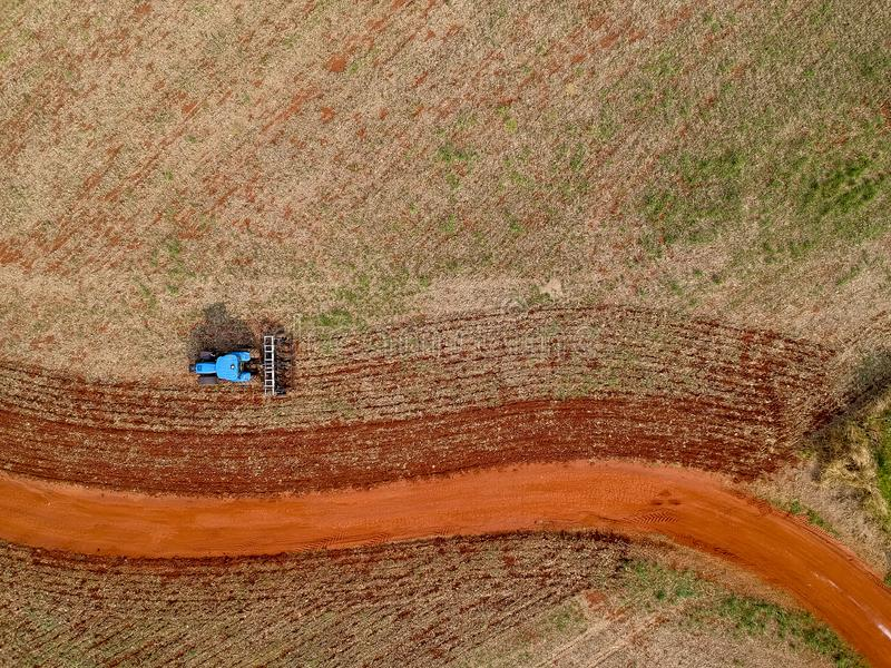 Aerial view of a tractor harrowing the soil to plant soybeans royalty free stock photo