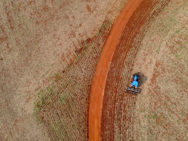 Aerial view of a tractor harrowing the soil to plant soybeans stock images