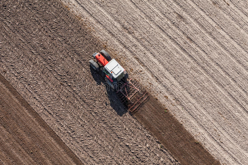 Aerial view of the tractor on the harvest field. Aerial view of the tractor working on the harvest field in Poland royalty free stock images
