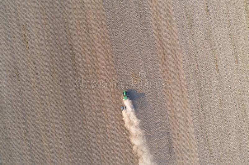 Aerial view on tractor ploughing field. stock photo
