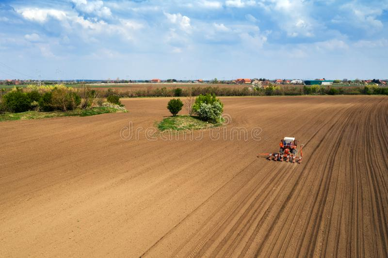 Aerial view of tractor sowing and planting corn in field royalty free stock image