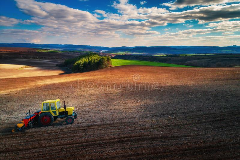 Aerial view of tractors working on the harvest field.  stock images