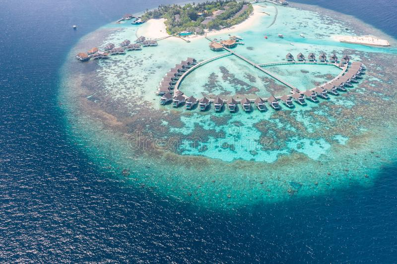 Aerial view of a tropical island in turquoise water. Luxurious over-water villas on tropical island resort maldives stock images