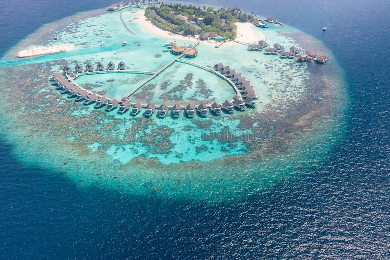 Aerial view of a tropical island in turquoise water. Luxurious over-water villas on tropical island resort maldives stock photography