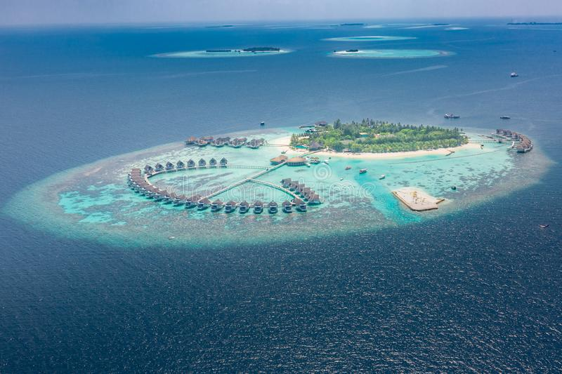 Aerial view of a tropical island in turquoise water. Luxurious over-water villas on tropical island resort maldives. Aerial view of water bungalow and blue sea stock photo