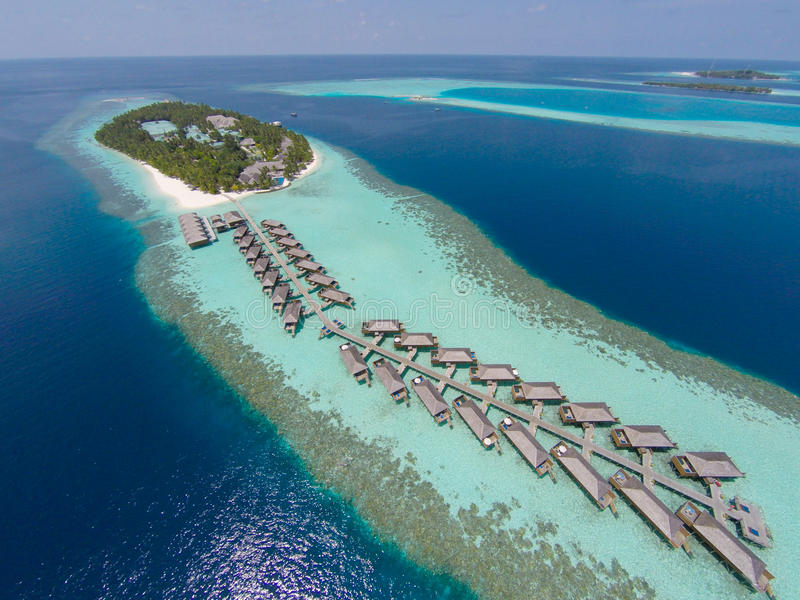 Aerial view of a tropical island in turquoise water. Luxurious over-water villas on tropical island resort maldives for holiday. royalty free stock photography