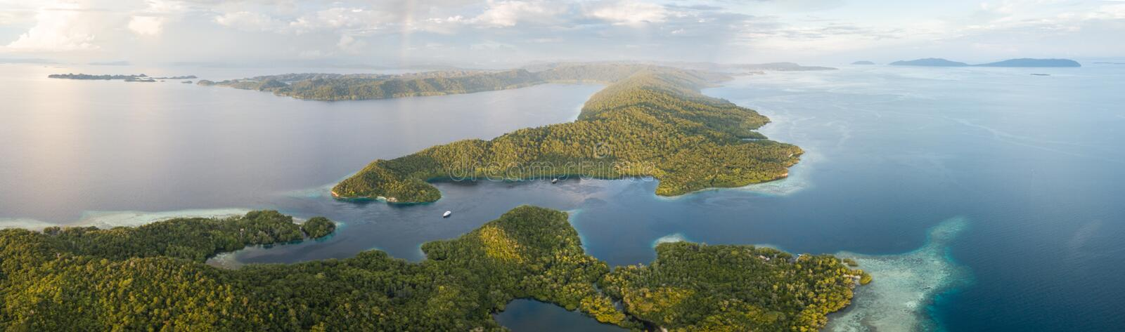Aerial View of Tropical Islands and Reefs in Raja Ampat. Clouds drift above a beautiful set of islands in Raja Ampat, Indonesia. This tropical region is known as stock images