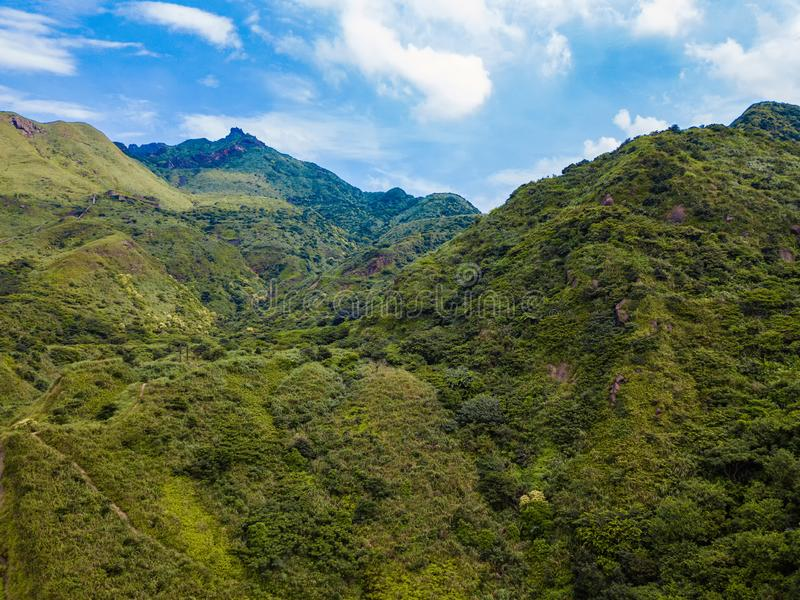 Aerial view of tropical trees in forest and mountain or hill with cloud sky at noon in New Taipei City, Taiwan. Natural landscape. Background stock photography