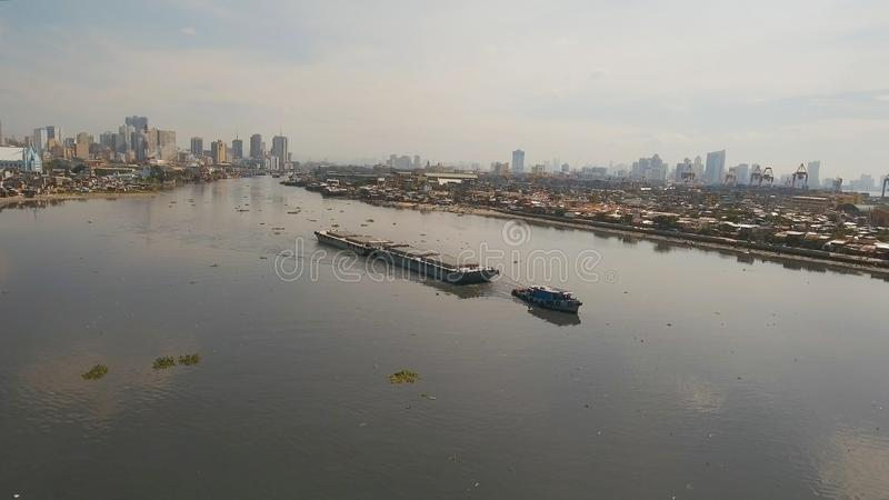 Aerial view tugboat and barge in the sea.Philippines, Manila. Aerial view tugboat pushes barge in the Bay of Manila. Tugboat and ship ine the harbor. Barge royalty free stock photos