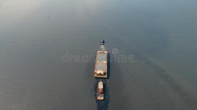 Aerial view tugboat and barge in the sea.Philippines, Manila. Aerial view tugboat pushes barge in the Bay of Manila. Tugboat and ship inside the harbor. Barge stock image