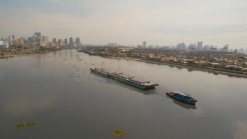 Aerial view tugboat and barge in the sea.Philippines, Manila. Aerial view tugboat pushes barge in the Bay of Manila. Tugboat and ship inside the harbor. Barge stock images