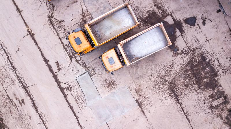 Aerial view of two orange trucks. in front of warehouse stock photo