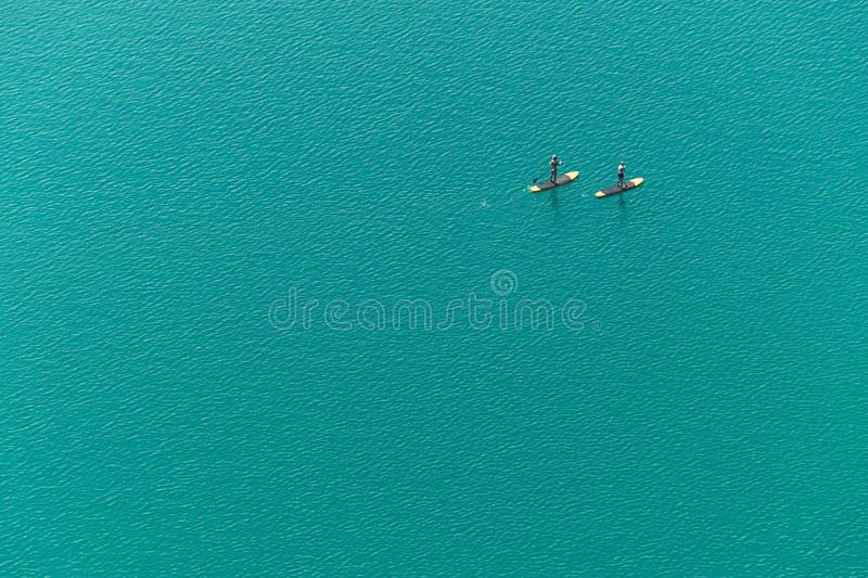 Aerial view of two unidentified stand up paddle boarders on the lake. Aerial view of two unidentified stand up paddle boarders on the turquoise water background royalty free stock images
