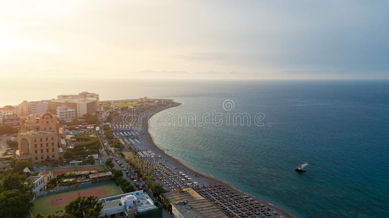 Aerial view of umbrellas, palms on the sandy beach at sunny day. Summer holiday in Greece. Blue sea and the Rhodes city. royalty free stock image