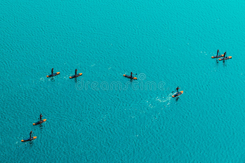 Aerial view of unrecognizable people stand up paddle boarding royalty free stock image