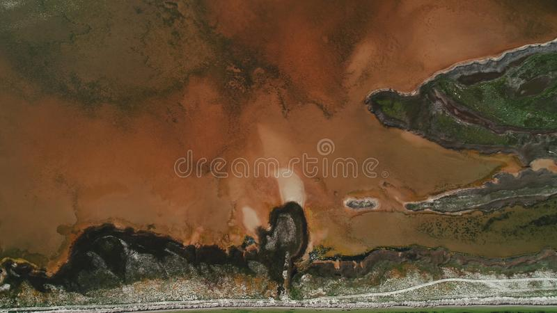 Aerial view of unusual dark island with brown earth, mangrove swamps and yellow reservoirs with dirty water, covered by stock photos