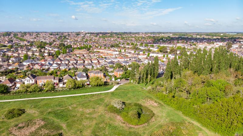 An aerial view of an urban area along a park under a majestic blue sky and white clouds.  stock photo