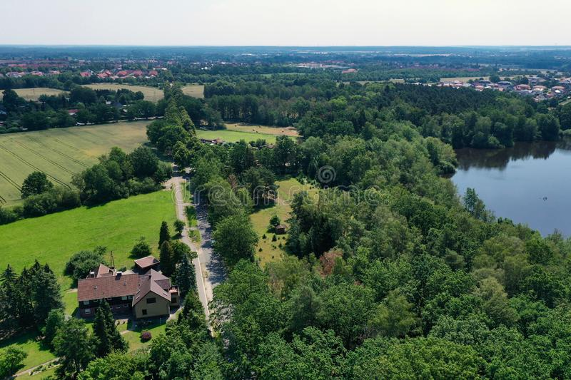 Aerial view from a vertical perspective of a house with big garden at the edge of a forest with a meadow in front of it stock image