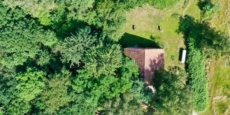 Aerial view from a vertical perspective of a small shed at the edge of a forest with a meadow in front of it stock images