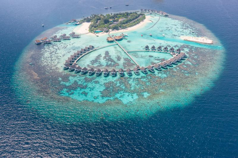 Aerial view of a tropical island in turquoise water. Luxurious over-water villas on tropical island resort maldives. Aerial view of water bungalow and blue sea royalty free stock photo