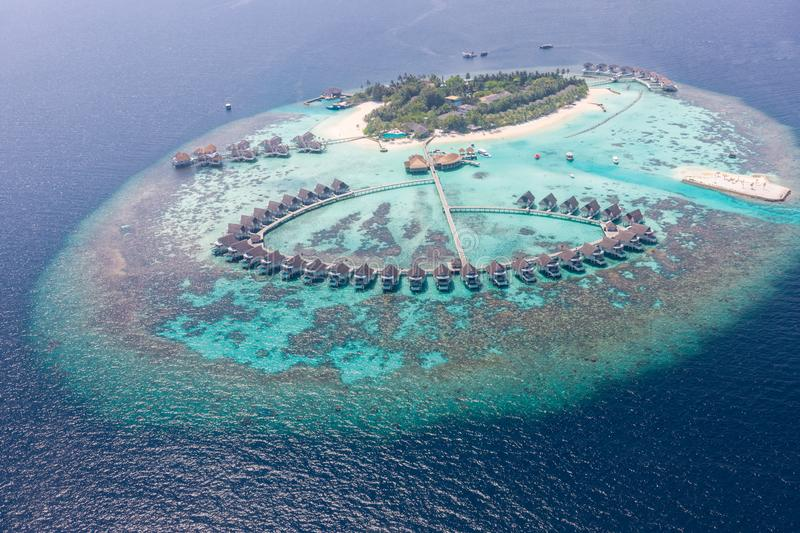 Aerial view of a tropical island in turquoise water. Luxurious over-water villas on tropical island resort maldives stock photos