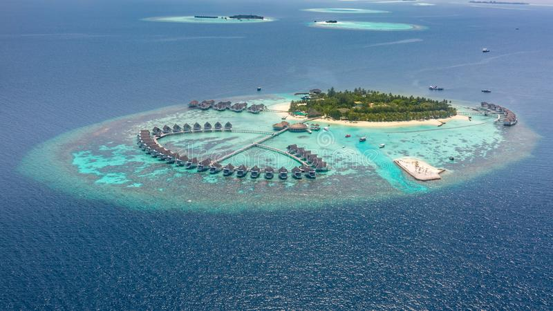 Aerial view of a tropical island in turquoise water. Luxurious over-water villas on tropical island resort maldives. Aerial view of water bungalow and blue sea stock photography