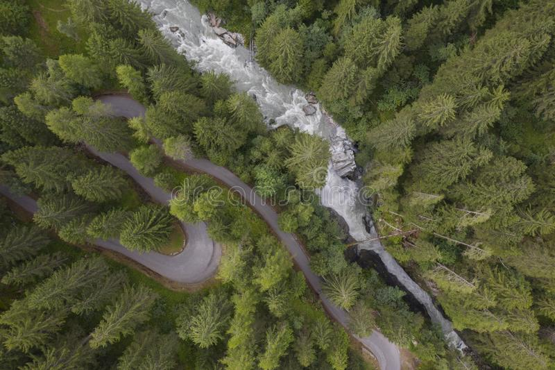 .aerial view of a waterfall and a mountain road winding through a fir forest. Photo taken with a drone flying over an S shaped road in a conifer and an waterfall stock photos