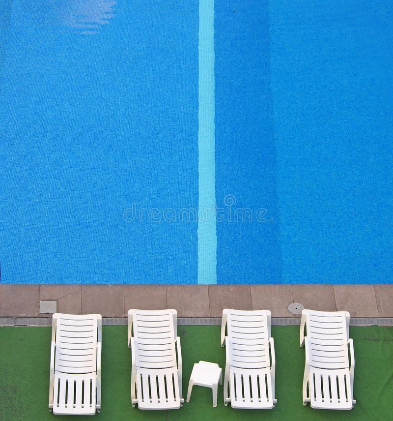 Aerial view of white sunbeds at the side of a blue swimming pool with bright water and a stripe in the tiles stock image