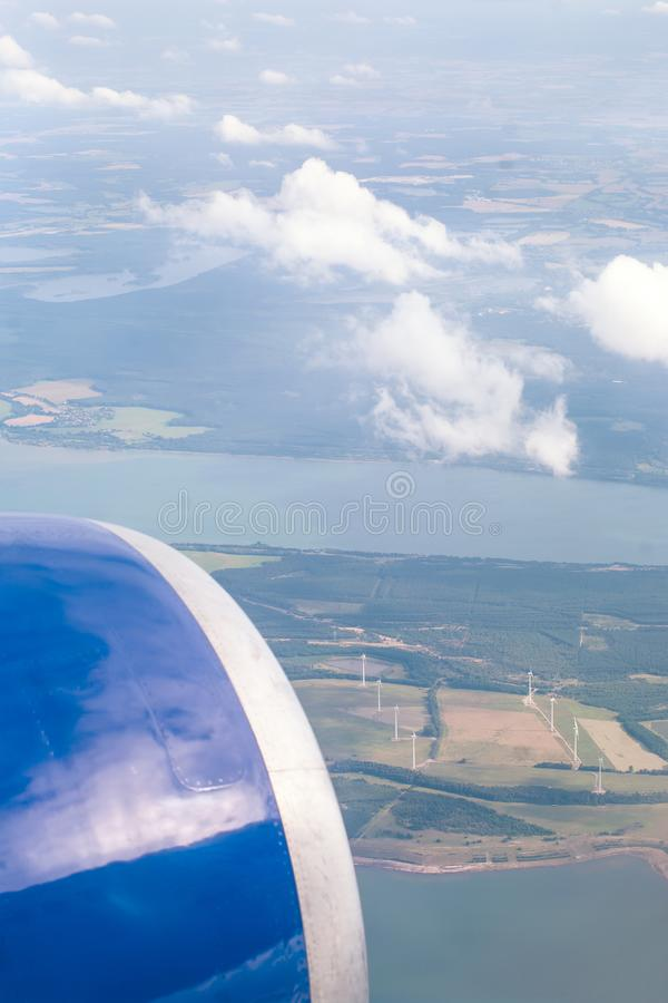 Aerial view of a wind farm with electric generators from aircraft window. Airplane flying above land with many fields and clouds stock photography