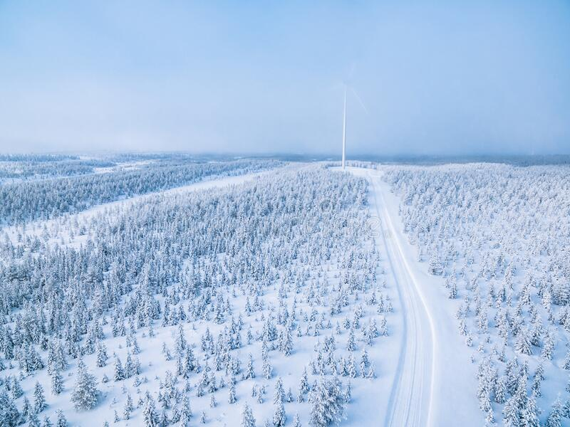 Aerial view of windmill in winter forest with snow road in Finland stock images