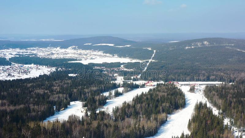 Aerial view of winter landscape with snowy pine forest and ski resort with funiculars. Footage. Top view of endless stock photos