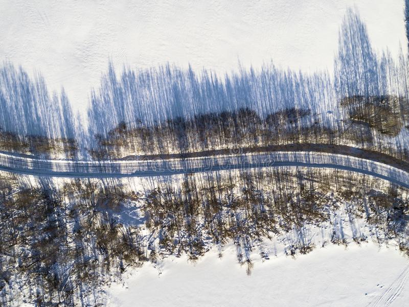 Aerial view of a winter road between two frozen lake. Winter landscape countryside. Aerial photography of snowy forest and frozen. Lake with road. Captured from royalty free stock image