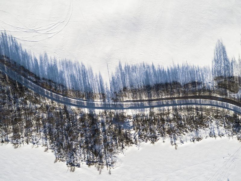 Aerial view of a winter road between two frozen lake. Winter landscape countryside. Aerial photography of snowy forest and frozen. Lake with road. Captured from royalty free stock photos