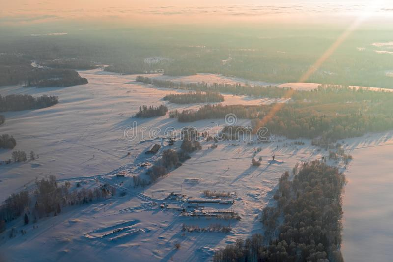 Aerial view winter sunrise over snow-covered space of the forest territory. Aircraft photography from above. stock photos