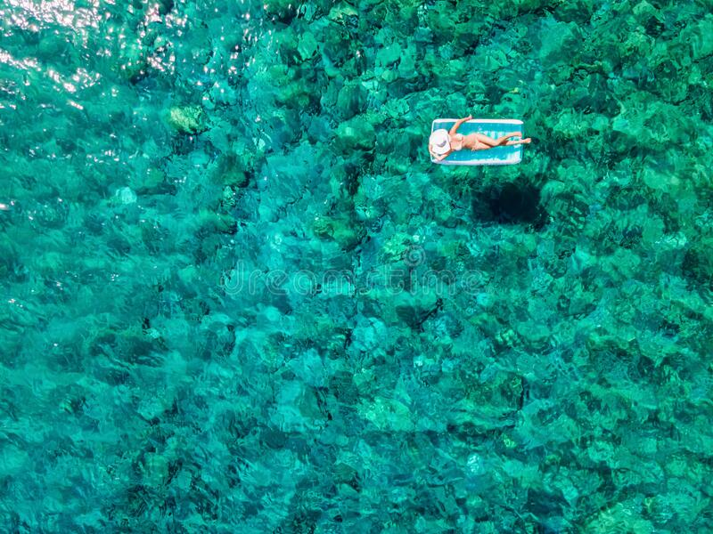 Aerial view of a woman in bikini on a inflatable matress drifting over turquoise water stock images