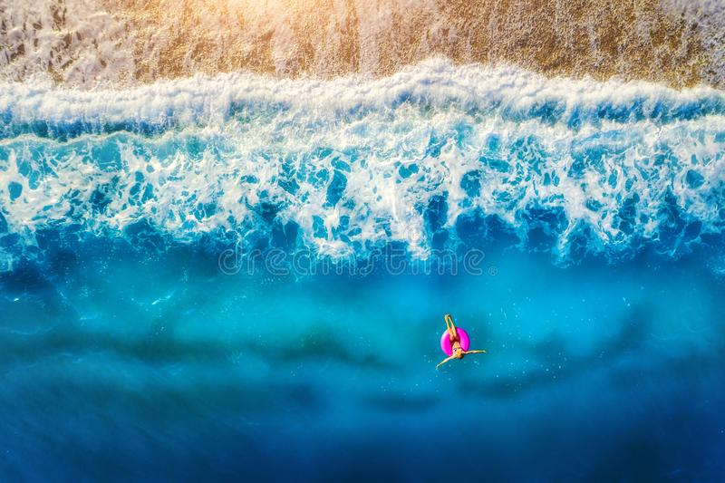 Aerial view of woman swimming on the pink swim ring in the sea. In the morning in Europe. Summer landscape with girl, beach, blue water, beautiful waves at royalty free stock images